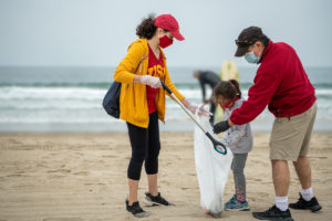 A woman, man and child wearing USC gear place garbage into a trash bag on the sand with the ocean in the background